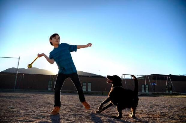 Eleven-year-old Zach Tucker, a fifth-grader at Otero Elementary in Colorado Springs, gets some exercise with his dog, Clyde, at a park near his home.