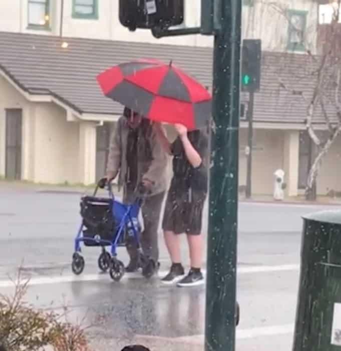 cậu bé lao ra ngoài trời mưa đá che ô cho cụ già