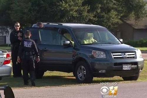 Cảnh sát điều tra chiếc xe hơi nơi cậu bé tử vong. Ảnh: CBS