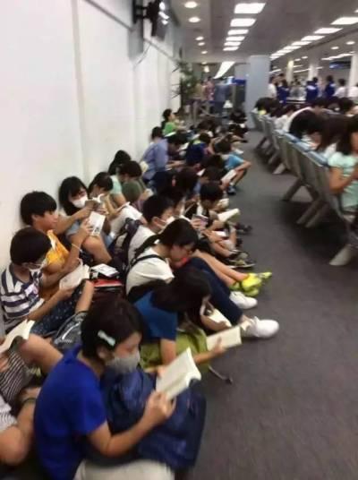 Trong lúc chờ đợi ở sân bay, hàng chục em học sinhNhật Bản ngay ngắn ngồi trên sàn nhà, tất cả cùng im lặng đọc sách. (Ảnh: Facebook)