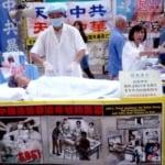 Người tu Pháp Luân Công mô phỏng cảnh thu hoạch nội tạng trên đường phố Hồng Kông. (Ảnh: Cory Doctorow/Flickr)