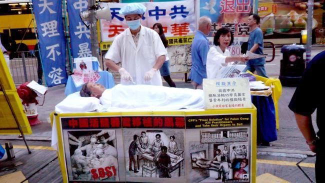 Người tu Pháp Luân Công mô phỏng cảnh mổ cướp nội tạng trên đường phố Hồng Kông. (Ảnh: Cory Doctorow/Flickr)