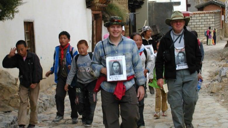 Người nhà của Sneddon mang ảnh của anh đến Vũ Hán để tìm người năm 2004