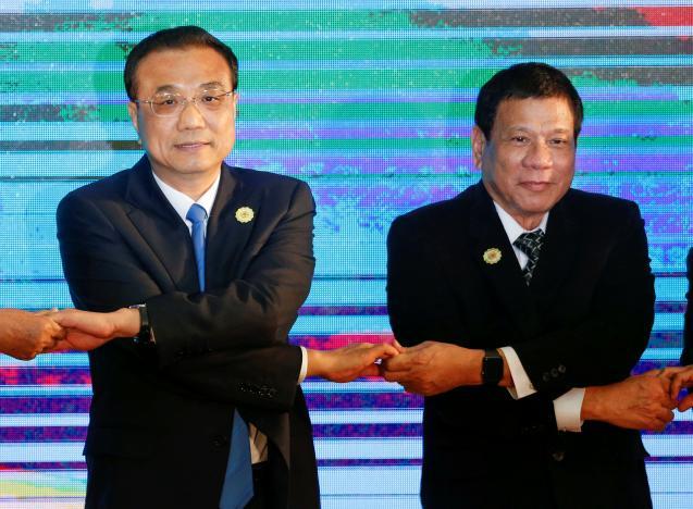 Tổng thống Philippines Rodrigo Duterte và Thủ tướng Trung Quốc Lý Khắc Cường bắt chéo tay trong Thưởng đỉnh ASEAN tại Lào 6/9/2016