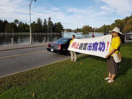 """Người tu Pháp Luân Công giơ biểu trưng """"Ngừng bức hại Pháp Luân Công"""" trên đường đến khách sạn (Ảnh: Tiểu Nguy)"""