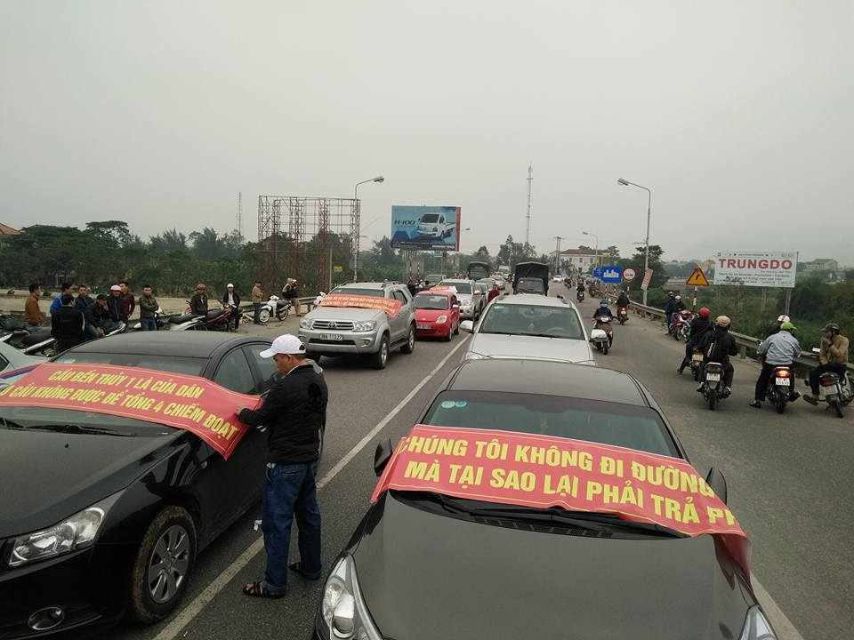 Người dân đưa khoảng 30 ô tô lên dừng đỗ, dán băng rôn tại đầu cầu Bến Thủy (Hà Tĩnh) để phản đối việc thu phí hôm 3/12. (Ảnh: FB Đức Cầu Bùng)