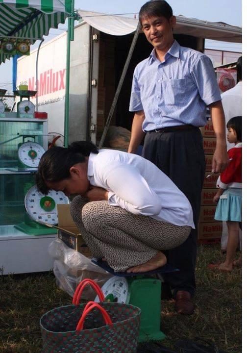 Một chị nông dân với kiểu thử cân Nhơn Hòa độc đáo, đứng cạnh là a Terence Vũ.