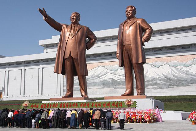 Người dân Bắc Triều Tiên đang cúi đầu trước tượng của ông Kim Il-sung (trái) và ông Kim Jong-il. (Ảnh: wiki)