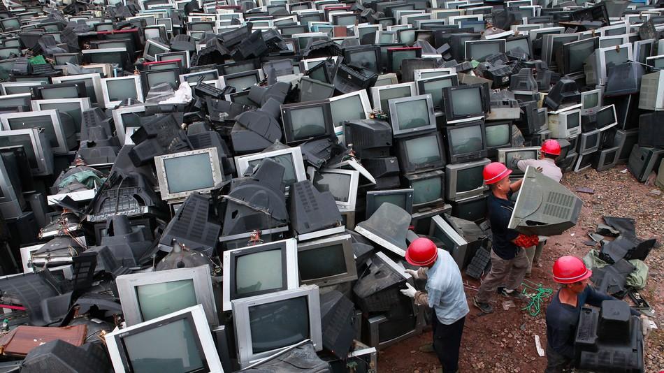 Các công nhân Trung Quốc đang vận chuyển các tivi bóng đèn điện tử cũ để tái chế tại một sân tập kết trong thành phố Nội Giang, Tứ Xuyên, năm 2013 (ảnh: Liu Aiguo - ImageChina)