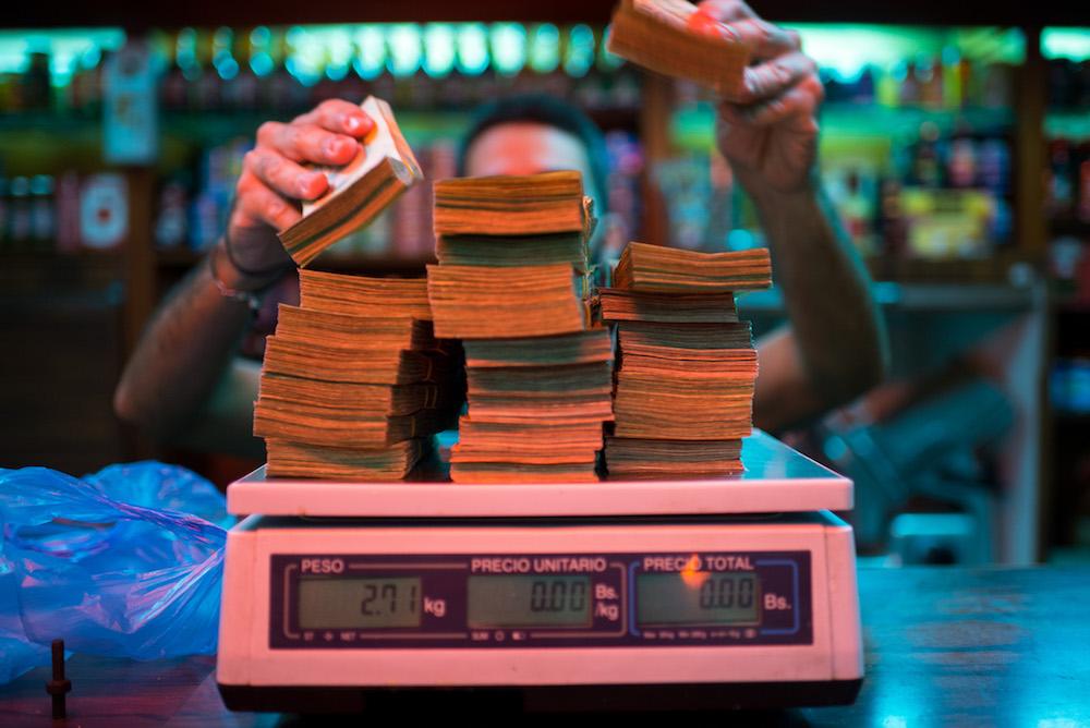 Chủ cửa hàng Venezuela cân tiền thanh toán (Ảnh: Bloomberg)