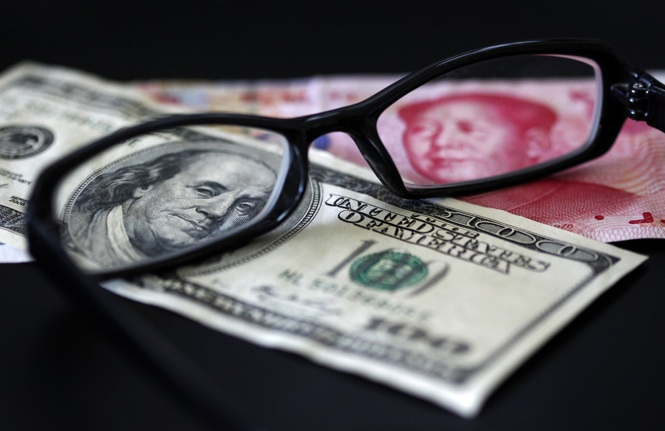 A U.S. dollar note (L) and a Chinese yuan banknote are seen through a pair of spectacles in this picture illustration taken in Taipei October 13, 2010. China's foreign exchange reserves soared in the third quarter and its trade surplus remained hefty, showing that the country is under both economic and political pressure to let the yuan rise more quickly. REUTERS/Nicky Loh (TAIWAN - Tags: BUSINESS)