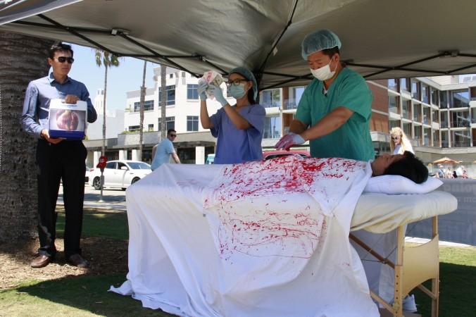 Người tập Pháp Luân Công nâng cao nhận thức của người dân địa phương và khách du lịch về hành động mổ cướp nội tạng và tội ác nhân quyền tại Trung Quốc tại Santa Monica, California, ngày 17/7/2016.