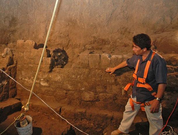 Trưởng dự án khai quật, Sergio Gomez, xem xét một phần bức tường đá của đường hầm. Vết nước ở cao, kéo dài suốt chiều dài đường hầm, cho thấy nước là một thành phần quan trọng trong một phản ứng nào đó (ảnh: The Yucatan Times)