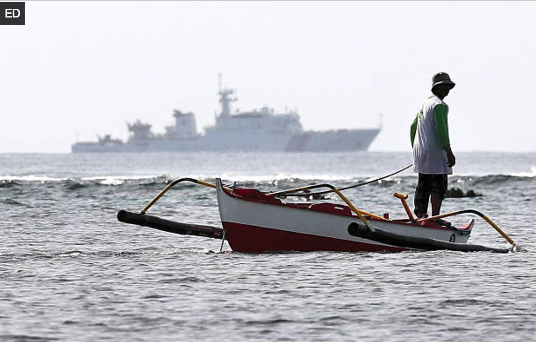 Ngư dân Philippines đánh bắt cá tại bãi cạn Scarborough, phía xa là con tàu tuần duyên cỡ lớn của Trung Quốc (ảnh: Getty)