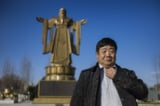 To go with AFP story China-politics-philosophy-sculpture,FEATURE by Benjamin Haas This picture taken on December 12, 2014 shows former general Wang Dianming posing next to a Confucius statue in the seaside resort in Beidaihe, Hebei province. Arms outstretched like Rio de Janeiro's Christ the Redeemer, a towering Confucius statue stands in the seaside resort that hosts the Chinese Communist leadership's summer retreat, opposite a hulking monument to President Xi Jinping's dreams. AFP PHOTO / FRED DUFOUR