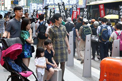 Một gia đình dừng chân bên đường quan sát cuộc diễu hành