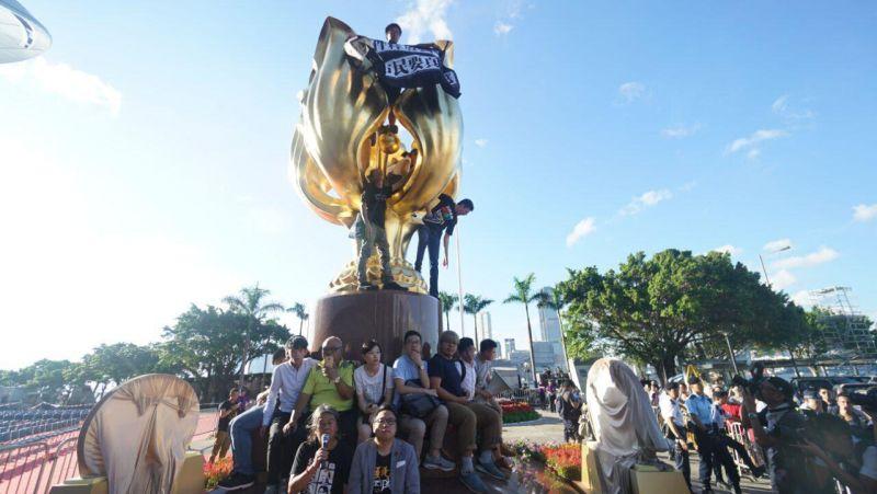 Người biểu tình ngôi xung quanh và trèo lên tượng Kim Tử Kinh