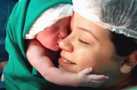 Bé gái mới chào đời đã vừa khóc vừa ôm chặt lấy mặt mẹ (Video)