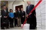 Tổng thống Donald Trump cắt tấm băng đỏ giữa hai chồng giấy tờ, tượng trưng cho các quy định của chính phủ trong những năm 1960, và các quy định của ngày hôm nay, hôm 14/12/2017
