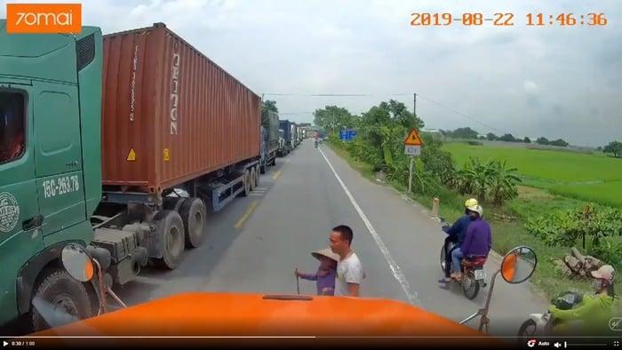 Tài xế container dắt bà cụ qua đường