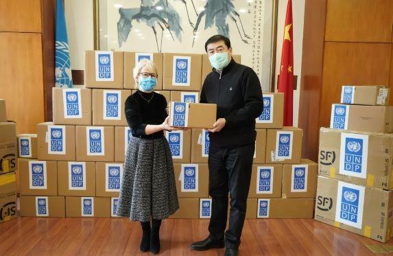 Đại diện của Liên Hiệp Quốc (bên trái) quyên tặng vật tư y tế trị giá 500.000USD cho Bộ Thương mại Trung Quốc, gồm điện tâm đồ (ECG) và bơm tiêm truyền.