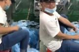 Nội dung video là là một người đàn ông được cho là nhân viên trong nhà máy sản xuất khẩu trang, đang ngồi bên cạnh dây chuyền sản xuất, dùng kiểu khoe khoang nhặt một nắm lớn khẩu trang dưới đất để lau giày của mình