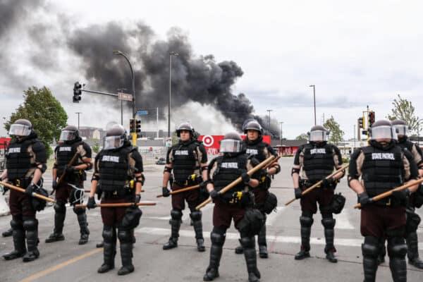 Ngày 29/5/2020, Cảnh sát đang đứng canh gác khi các cột khó từ các tòa nhà tiếp tục bùng lên do hậu quả từ một đêm biểu tình và bạo loạn sau cái chết của George Floyd tại Minneapolis. (Ảnh: Charlotte Cuthbertson/The Epoch Times)