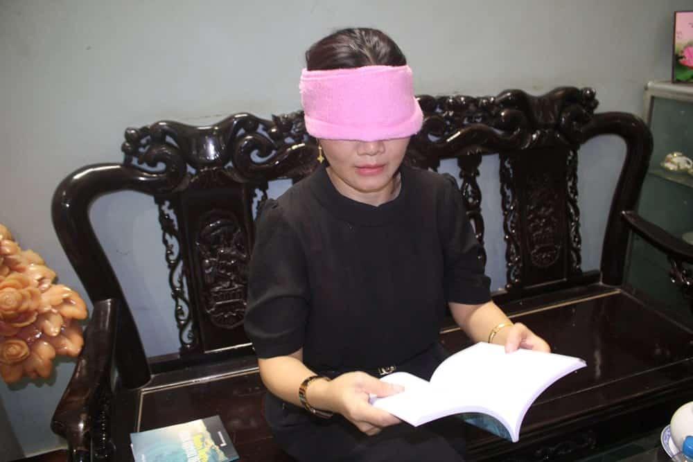 Chị Hoàng Thị Thiêm có thể đọc sách trong khi mắt bị bịt kín (ảnh: kienthuc.net.vn)